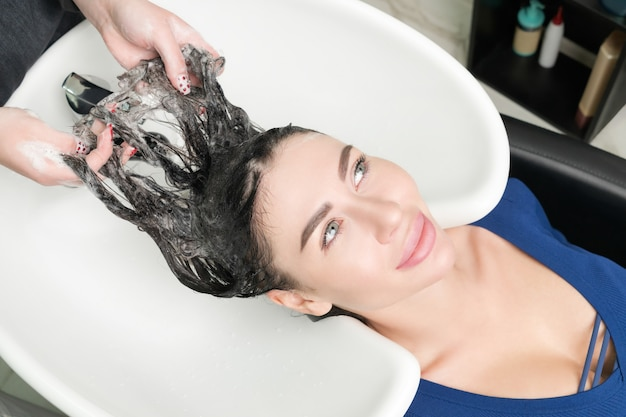 Hairstylist's hands wash long hair of caucasian brunette woman with shampoo in professional sink for shampooing in beauty salon.