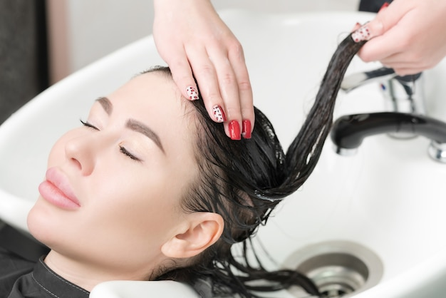 Hairstylist's hands wash long hair of glamour brunette woman with shampoo in professional sink for shampooing in beauty and hair salon.