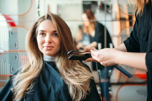 Парикмахер выпрямляет волосы утюжком, клиентка в парикмахерской. прически в салоне красоты, парикмахер делает прическу