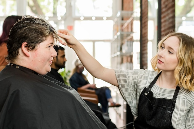 Hairstylist trimming hair of the customer in a beauty salon