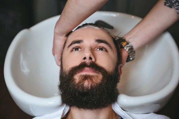 理髪店でひげを持つ若い魅力的な男の頭を洗うヘアスタイリスト
