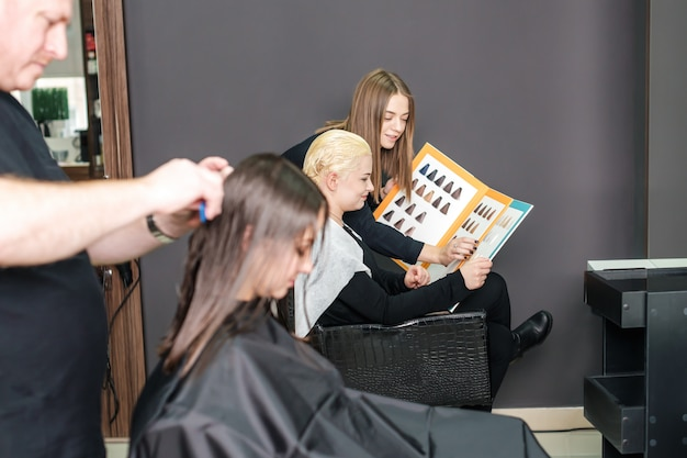Hairstylist with catalog is choosing hair color for female customer at parlor.