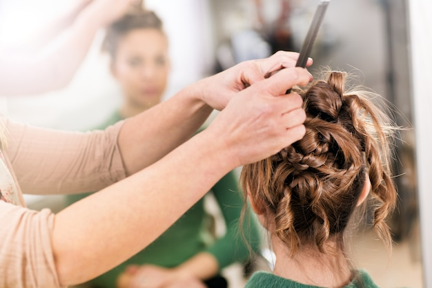 Hairstylist working on womans hairdo in close-up