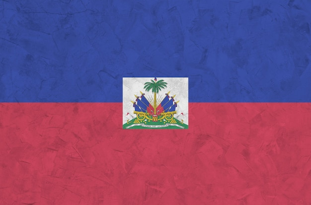 Haiti flag depicted in bright paint colors on old relief plastering wall. textured banner on rough background