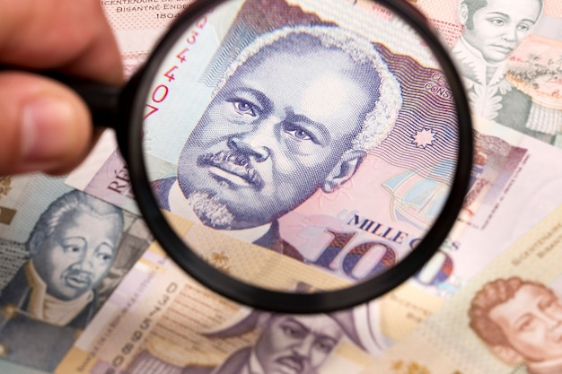 Haitian money in a magnifying glass a business background
