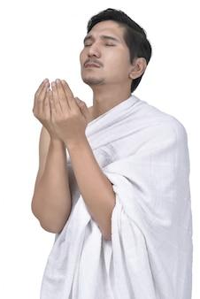 Hajj布で宗教的なアジアのイスラム教徒の男性が祈る