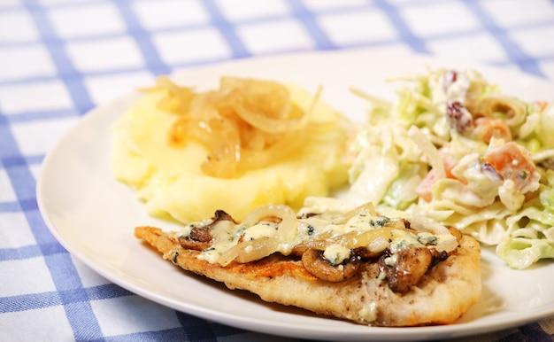 Рыба хек, запеченная с грибами, подается с картофелем и салатом