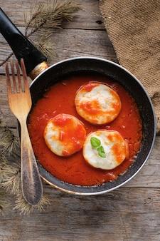 素朴な木製のテーブルの上のフライパンでトマトとメルルーサのメダリオン