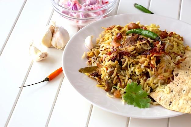 Halal indian chicken biryani served with yogurt tomato raita over white background. selective focus.