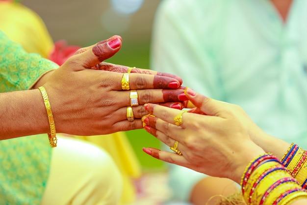インドの結婚式の写真、haldi式新郎新婦の手