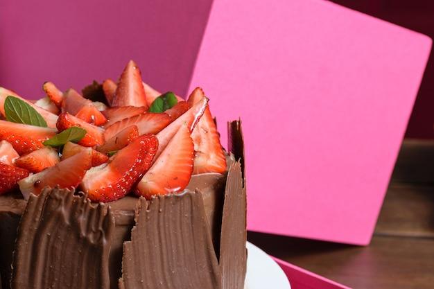 イチゴ、バジルの葉、ブラックベリージャム、チョコレートプレートが周りにあるチョコレートケーキの半分。