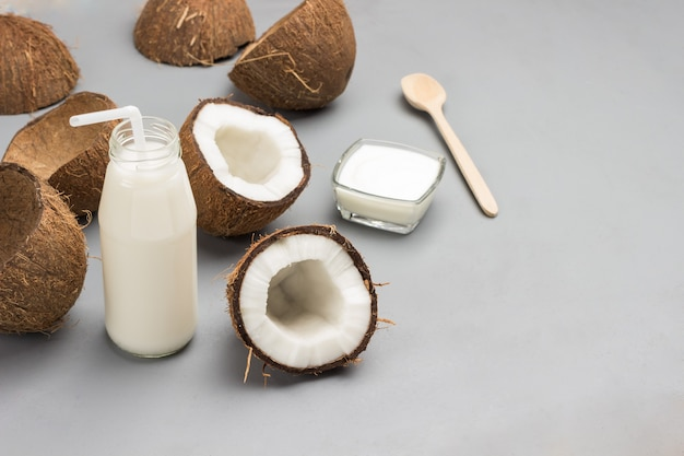 ココナッツの半分、ストローとココナッツミルクのボトル。