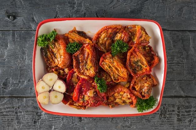 Половина чеснока и вяленых помидоров на деревянном столе. средиземноморская закуска из томатов. вегетарианская пища.