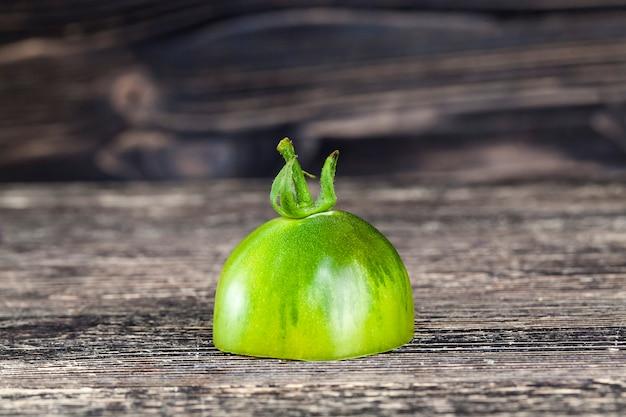 黒く塗られたボード上の半分の緑のトマト、クローズアップ