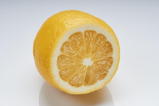 Половинка лимона на яркой глянцевой поверхности