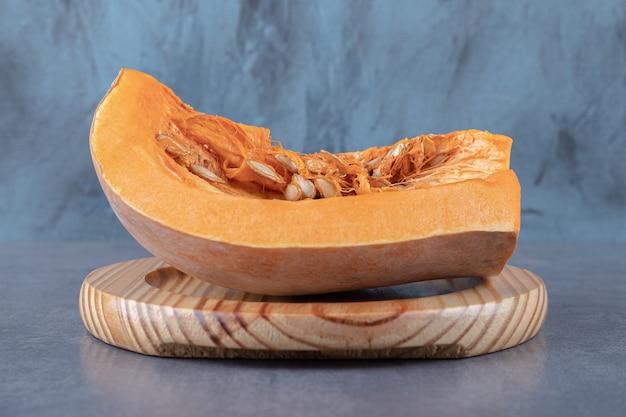大理石の表面に、木の板にかぼちゃを半分載せました。