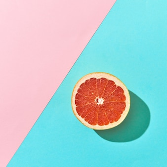テキスト用のスペースとダブルピンクとブルーの段ボールの背景に半分熟したグレープフルーツ。かんきつ類の果実。上面図