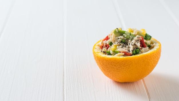 Половина апельсина с курицей и салатом из авокадо с перцем на белом столе. диетическое питание из тропических фруктов и курицы.