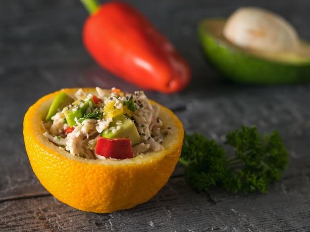 Половина апельсина с салатом на фоне перца и авокадо. диетическое питание из тропических фруктов и курицы.