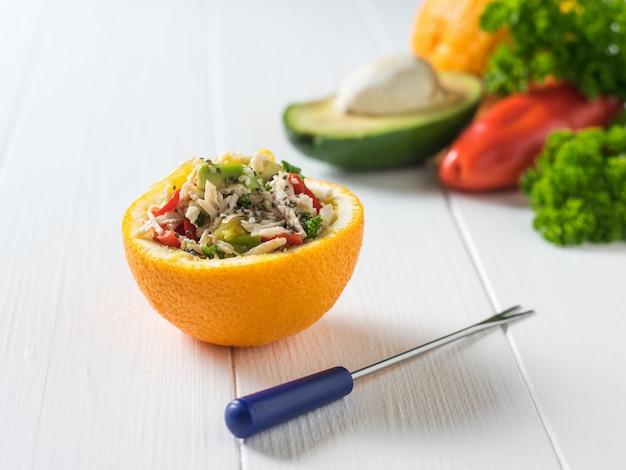 Половина апельсина с салатом, вилкой и овощами на деревянном столе. диетическое питание из тропических фруктов и курицы.