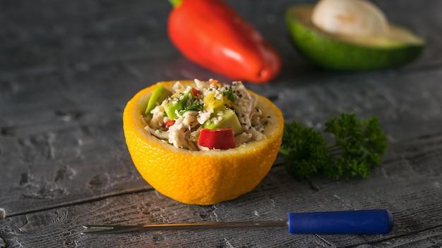 Половина апельсина с салатом, перцем и авокадо с вилкой на деревянном столе. диетическое питание из тропических фруктов и курицы.