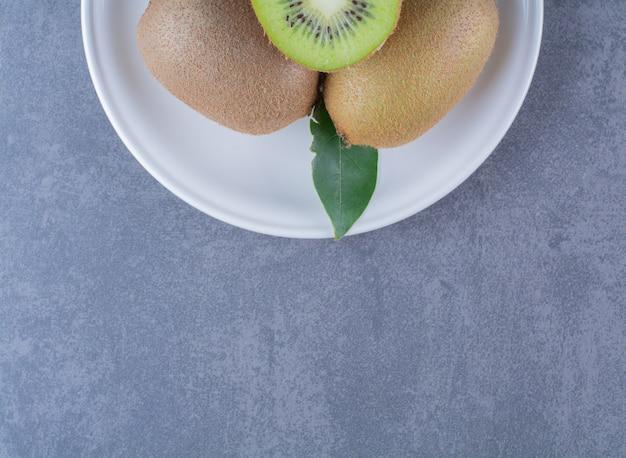 Половина и целые плоды киви на тарелке на мраморном столе.