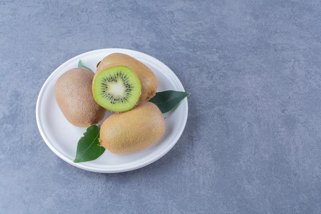 Половина и целые плоды киви на тарелке на темной поверхности