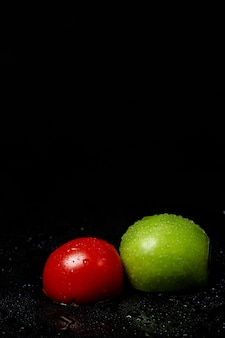 Half apple and tomato on a black