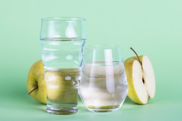 Half apple and water glasses on green background