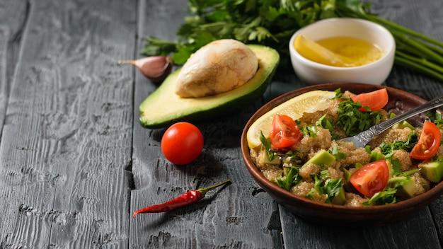半分のアボカド、唐辛子、トマト、暗い素朴な黒い木製のテーブルにサラダのボウル。