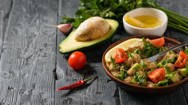 Half avocado, chili, tomato and a bowl of salad on a dark rustic black wooden table.