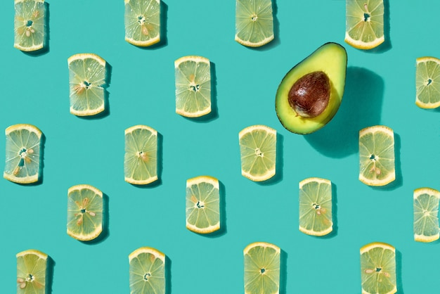 Half an avocado and juicy lemon slices on a blue background. creative food pattern for layout. flat lay
