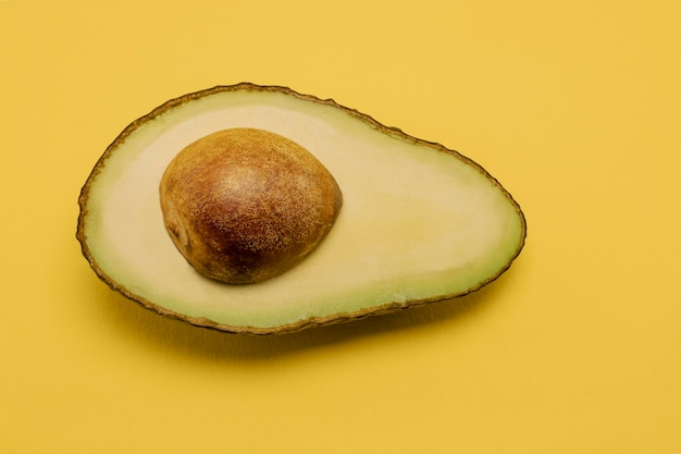 Half avocado on pastel yellow background. minimalism and objects on a simple background.
