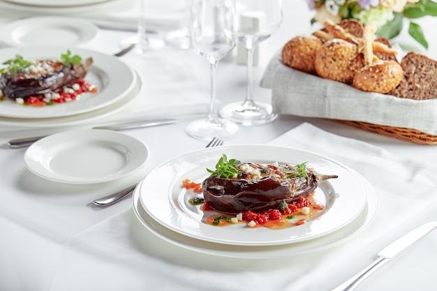 白い背景に肉、チーズ、トマトと半分焼きナス。宴会のお祭り料理。グルメレストランメニュー。白色の背景。