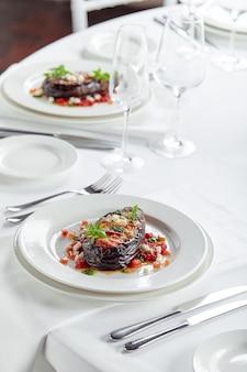 Наполовину запеченные баклажаны с мясом, сыром и помидорами на белом фоне. банкетные праздничные блюда. меню ресторана для гурманов. белый фон.