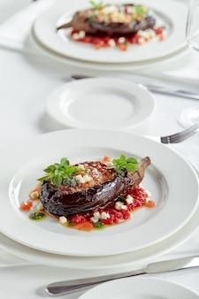 흰색 바탕에 고기, 치즈, 토마토를 넣은 반쯤 구운 가지. 연회 축제 요리. 미식식당 메뉴판. 흰 바탕.