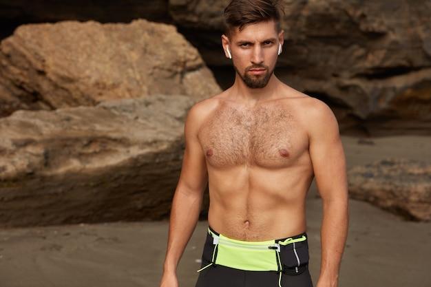 Uomo sportivo mezzo nudo con barba incolta, espressione seria