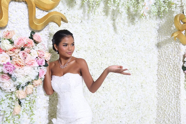 반신 20대 그을린 피부 아시아 신부는 레이스 베일, 검은 머리가 달린 흰색 웨딩 드레스를 입는다. 소녀는 꽃 장식 벽 위에 행복한 미소를 표현하고, 사랑스러운 스타일의 스튜디오 복사 공간