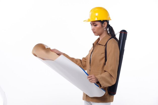 Half body figure of 20s asian beautiful woman engineer wear safety hard hat. architecture female stands and carry construction blueprint roll tube over white background isolated