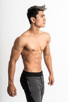 Изображение половинного тела азиатского молодого человека, показывающего мускулистый живот, стоящий лицом к стороне