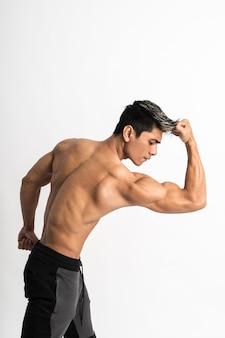 上腕二頭筋の筋肉スタンドを示す若い男の半身画像が前を向く