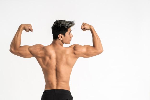 Половина тела изображение молодого человека показывает мускулистое тело стоять лицом назад