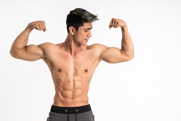 Half body image of young man showing muscular biceps stand facing forward