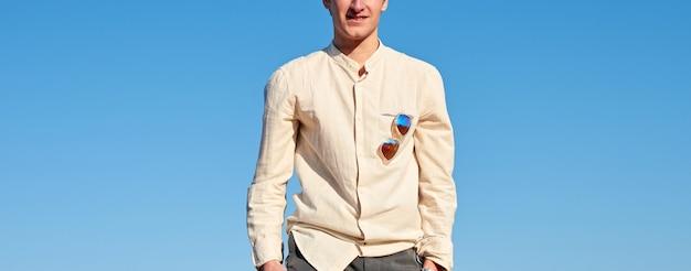 베이지 색 셔츠와 선글라스를 착용 한 젊은 남자의 절반 시체