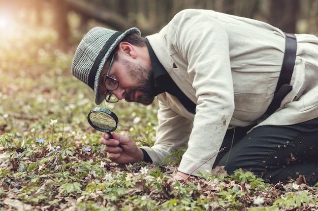 Половина тела человека презентабельного вида, изучающего растительность через лупу, стоящего на коленях на земле в парке