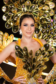 Half body portrait of asian transgender woman in cabaret carnival fancy gold fish scales dress gown wing head set over dark background