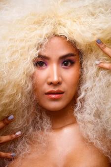 20 대 아시아 백인 아름 다운 여자 금발 아프리카 머리 높은 패션의 절반 본문 초상화 메이크업. 귀여운 소녀 미소는 스튜디오의 파스텔 빨간색 파란색 노란색 화려한 하늘 구름 위에 카메라를 쳐다봅니다.