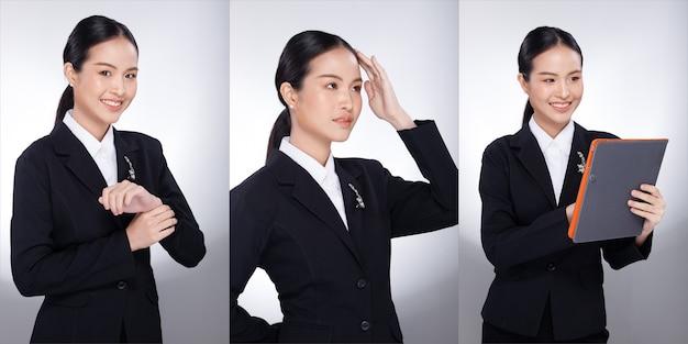 20대 아시아 여성 흑발 회색 정장 재킷의 반신 초상화. 사무실 소녀는 많은 표정을 짓고 흰색 배경 위에 디지털 태블릿을 사용합니다.