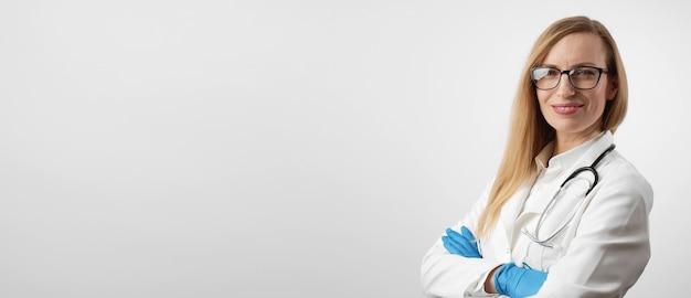 カメラを探している手術用手袋で腕を組んでポジティブな女性医師の半身の肖像画