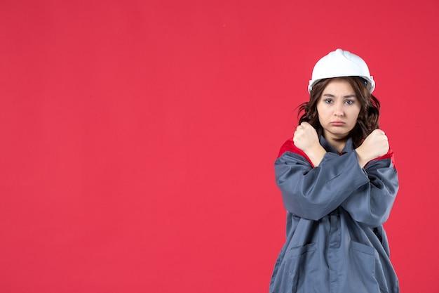Colpo a metà corpo di un costruttore femminile arrabbiato in uniforme con elmetto e che fa un gesto di arresto su sfondo rosso isolato